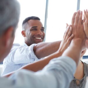 Shot of a group of colleagues giving each other a high five in an office